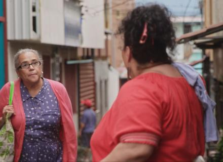Two neighbors talk on the street