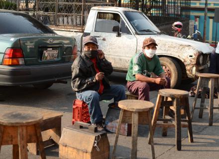 Dos hombres mayores con máscaras de protección ofrecen limpieza de zapatos en una ciudad centroamericana