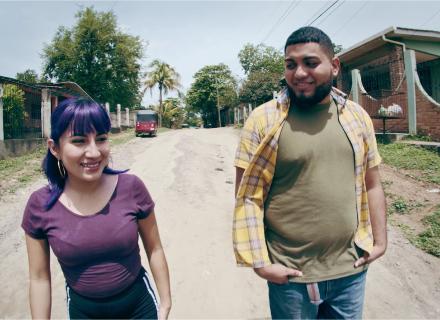 Una mujer y un hombre, ambos jóvenes y de aspecto, caminan por el centro de una calle polvorienta.