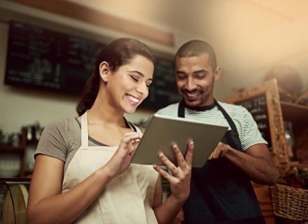 Hombre y mujer jóvenes con delantales contemplan tablet, mientras sonríen